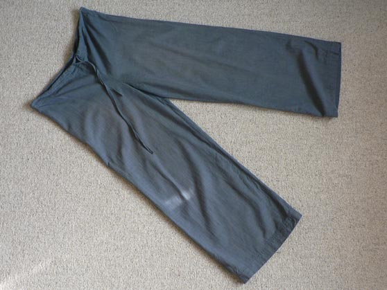 Blue-green cotton trousers laid flat