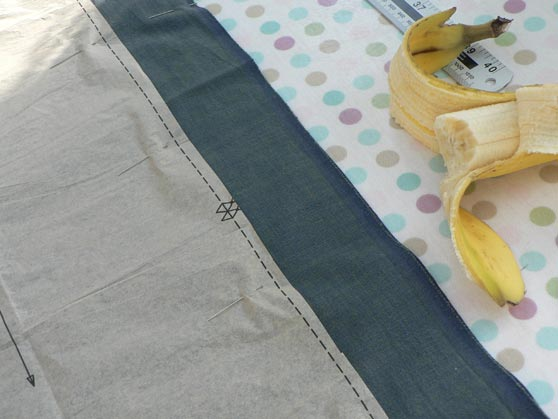 Fabric laid out on table with trouser pattern pieces pinned on, plus a ruler and half-eaten banana