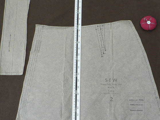 Pattern pieces and ruler on brown fabric