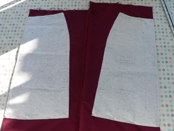 Pattern pieces pinned to burgundy cotton fabric