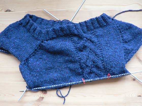 Top of Leaf T on knitting needles showing wonky armholes