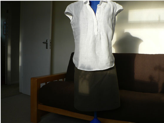 Olive-green skirt and white linen blouse on dressmakers dummy