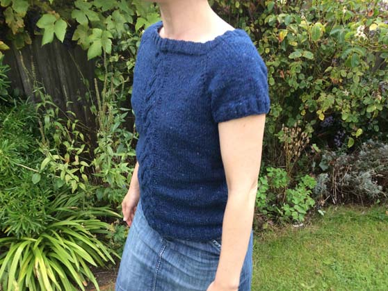 Me wearing blue knitted top in garden - front view