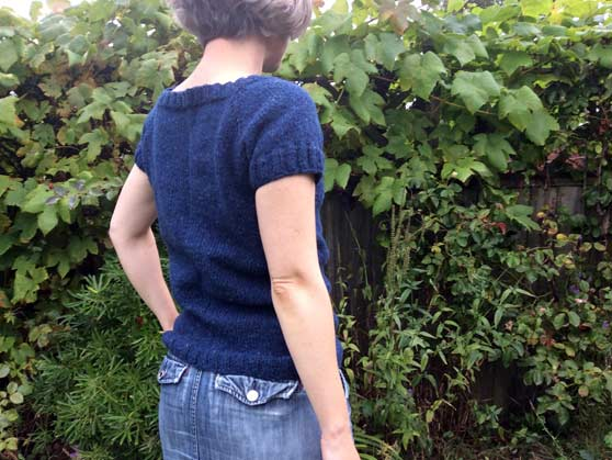 Me wearing blue knitted top in garden - back view